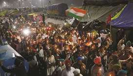 Farmers participate in a candlelight vigil to pay homage to paramilitary troops killed in a suicide