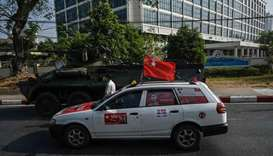 A car decorated to support the National League for Democracy (NLD) drives past a military vehicle pa