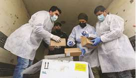 Palestinian workers unload the first shipment of coronavirus disease (Covid-19) vaccines, in the sou