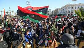 Libyans wave national flags as they gather in the capital Tripoli's Martyr's Square to celebrate the
