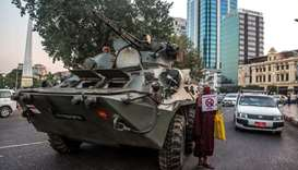 A Buddhist monk holding a sign stands next to an armoured vehicle during a protest against the milit