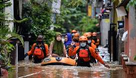 Volunteers evacuate elderly women with an inflatable boat in an area affected by floods, following h