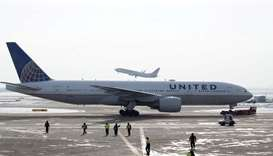 A United Airlines Boeing 777-200ER plane is towed as an American Airlines Boeing 737 plane departs f