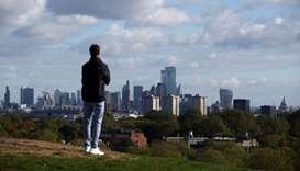 A person looks at the skyline of central London in the background, amid the outbreak of the coronavi