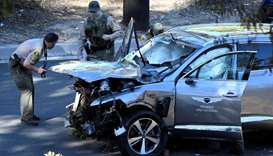 Los Angeles County Sheriff's Deputies inspect the vehicle of golfer Tiger Woods, who was rushed to h