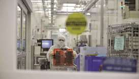 A technician pushes a cart of semiconductor wafers at the Applied Materials facility in Santa Clara,