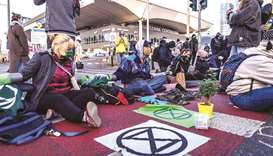 Activists of Extinction Rebellion (XR) environmentalist group form a chain yesterday as they block o