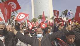 Supporters of the Ennahdha party wave national and party flags during a demonstration in support of