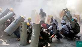 Protesters take cover as they clash with riot police officers during a protest against the military