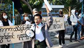 People protest on the street against the military after Monday's coup, outside the Mandalay Medical