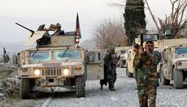 Afghan National Army soldiers inspect the site of a car bomb attack on a military base in Shirzad di