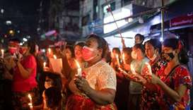 Women wearing red ribbons hold candles during a night protest against the military coup in Yangon, M