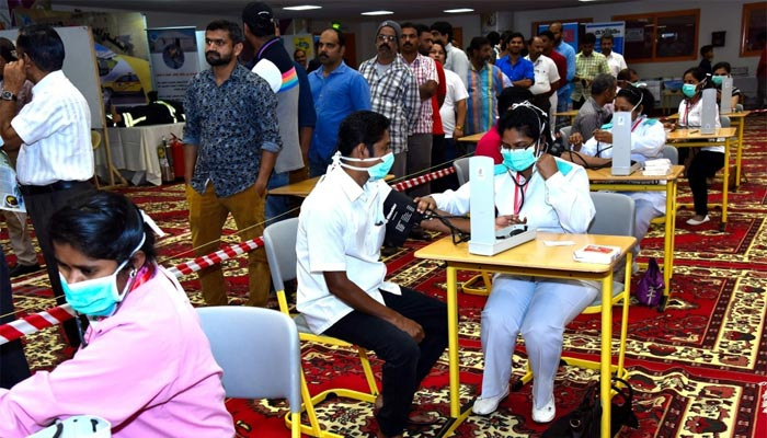 Workers get tested for blood pressure at the medical camp..