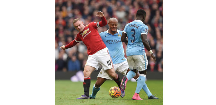 Manchester United's Wayne Rooney (L) is challenged by City's Belgian defender Vincent Kompany (C).