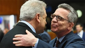 German Interior Minister Thomas de Maiziere (R) greets European Commissioner for Migration
