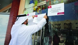 A ministry official putting a closure notice on the shop door