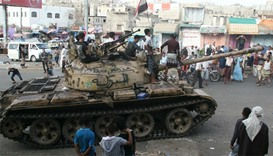 Pro-government fighters ride on a tank in the Bir Basha neighbourhood