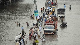 Pakistani commuters travel through a flooded street