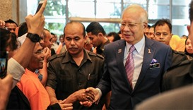 Malaysia's Prime Minister Najib Razak (C) shakes hands with supporters