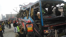 Pakistani security officials search the damaged bus after bomb blast in Peshawar