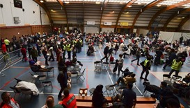 Travellers who were evacuated from Brussels airport take shelter at a sports complex in Zaventem