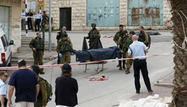 Israeli soldiers carry the dead body of one of two Palestinians