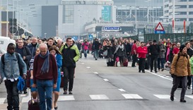 People walk away from Brussels airport after explosions rocked the facility in Brussels, Belgium Tue