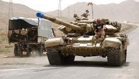 Syrian pro-governement forces drive a tank on the outskirts of Palmyra