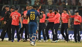 England players celebrate after winning as Sri Lanka's Angelo Mathews (C) walks off the pitch