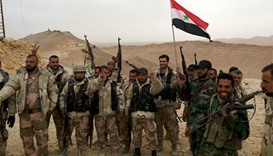 Forces loyal to Syria's President Bashar al-Assad flash victory signs in Palmyra