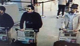 The footage shows the man wearing a hat and white jacket pushing a trolley with a large bag through