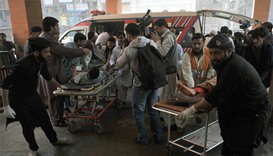 Pakistani security personnel and volunteers move victims injured in a suicide bombing in Shabqadar.