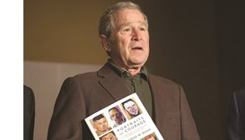 Bush with a copy of his Portraits of Courage painting exhibit.