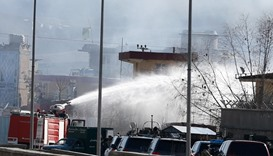Afghan firefighters spray water as they try to extinguish fire at the site of a blast and gunfire be