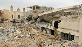 People inspect a damaged mosque after an airstrike on the rebel-held village of al-Jina, Aleppo prov
