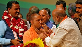 India's ruling Bharatiya Janata Party (BJP) leader Yogi Adityanath (C) is offered sweets