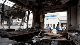 Indian private security guards look at the burnt reception office at the main gate of the Maruti Suz