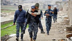 Iraqi Federal Police member carries his comrade during clashes with Islamic State militants, at Mosu