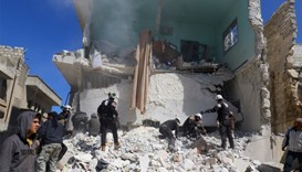 People and civil defence personnel remove rubble  after clashes in Idlib city