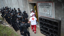 Riot police stand guard outside as Red Cross workers enter a juvenile detention center in San Jose P