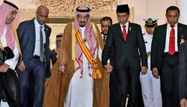 Saudi King Salman holds hand of  Indonesia President Widodo as they leave the presidential palace