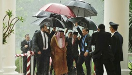 Saudi King Salman and Indonesian President Joko Widodo walk under umbrellas in heavy rain