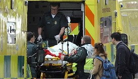 Paramedics load a victim into the back of an ambulance as members of the emergency services work on