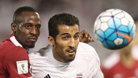 Iran's Vahid Amiri (R) and Qatar's Yasir Isa vie for the ball