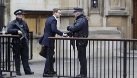British Member of Parliament Tobias Ellwood shakes hands with an armed police officer as he arrives
