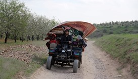 A Syrian man flees with his belongings from the village of Rahbet Khattab in the Hama province