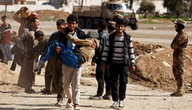 Displaced people are checked by Iraqi forces as Iraqi forces battle with Islamic State militants, in