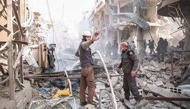 Syrian civil defence volunteers, known as the White Helmets, extinguish a fire following reported ai