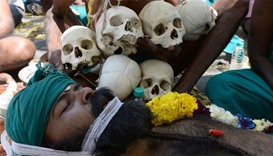 "An Indian farmer from the southern state of Tamil Nadu plays dead near symbolic ""skulls"" as he takes"