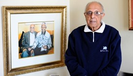 Ahmed Kathrada posing next to a picture of himself with Nelson Mandela in his house in Johannesburg.